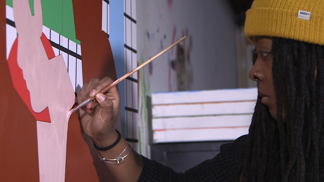 Nina Chanel Abney painting in her studio.